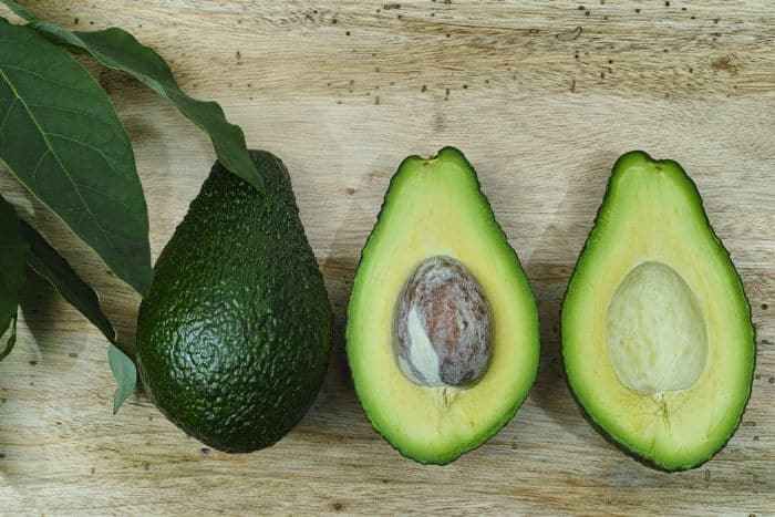 Image of whole and halved avocado