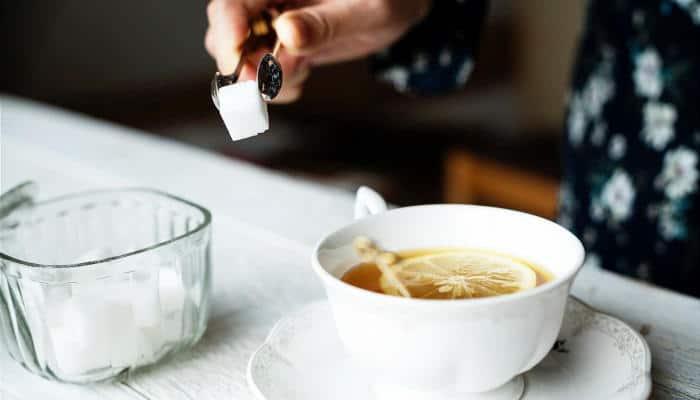 Person adding sugar to tea