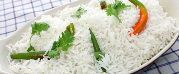 Plate of cooked basmati rice with cilantro and chillis